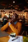 Peinzende Afrikaans-Amerikaanse Mens in koffie stock afbeeldingen