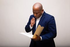 Peinzende Afrikaanse Amerikaanse Zakenman Looks Through Folder royalty-vrije stock foto's