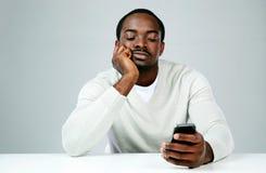 Peinzende Afrikaanse mens die smartphone gebruiken royalty-vrije stock fotografie