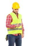 Peinzende arbeider die een tekstbericht verzenden Stock Foto's