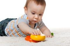 Peinzende babyjongen met speelgoed Royalty-vrije Stock Afbeelding
