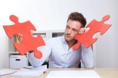 Peinzende bedrijfsmens met figuurzaag Stock Fotografie