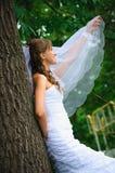 Peinzende bruid in witte kleding die en sluier bevinden zich houden Stock Afbeeldingen