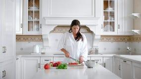 Peinzende ernstige vrouwelijke hakkende groenten die maaltijd voorbereiden die bij luxe uitstekende keuken zich thuis bevinden stock videobeelden