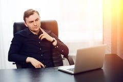 Peinzende geconcentreerde redacteur die nieuw artikel controleren op zijn laptop royalty-vrije stock afbeeldingen