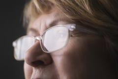 Peinzende Hogere Vrouw die Glazen dragen royalty-vrije stock afbeeldingen