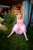 Peinzende jonge blonde vrouw in roze kleding Stock Afbeeldingen