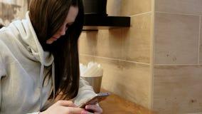 Peinzende jonge donkerbruine vrouw in een helder overhemd die in haar cellphonezitting werken in koffie stock videobeelden