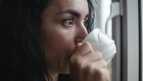 Peinzende jonge Kaukasische vrouw die de regen buiten de venster het drinken koffie bekijken stock footage