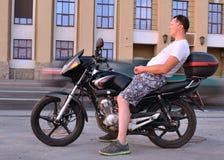 Peinzende jonge mens met motorfiets Royalty-vrije Stock Foto