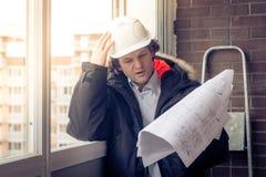Peinzende jonge mensenbouwer in bouwvakker standng en denkend Zachte gestemde nadruk, stock afbeeldingen
