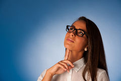 Peinzende jonge Spaanse vrouw die voor blauwe backgroun denken Royalty-vrije Stock Afbeeldingen