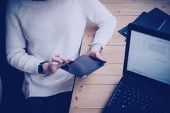 Peinzende jonge vrouw die moderne digitale tablet en laptop met behulp van terwijl het zitten op haar werkende plaats in het cowo stock foto's