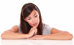 Peinzende jonge vrouw die terwijl neer het kijken benieuwd zijn Stock Afbeeldingen