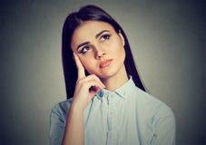 Peinzende jonge vrouw in twijfels stock afbeeldingen