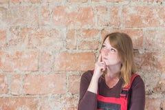Peinzende jonge vrouw voor een bakstenen muur Royalty-vrije Stock Afbeeldingen