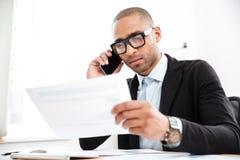 Peinzende jonge zakenman die documenten in bureau bekijken stock fotografie