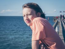 Peinzende jongen op een pijler bij Oostzee stock afbeeldingen