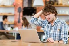 Peinzende kerel die en laptop in koffie denken met behulp van royalty-vrije stock foto's