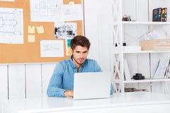Peinzende knappe gebaarde toevallige zakenmanzitting met laptop Stock Afbeeldingen