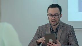 Peinzende leraar met de computer van tabletpc in klasse stock video