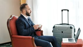 Peinzende mannelijke zakenman het drinken thee of koffiezitting op uitstekende leunstoel die van rem genieten stock footage