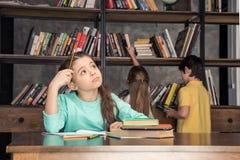 Peinzende meisjeszitting bij lijst met klasgenoten die boeken erachter zoeken stock fotografie