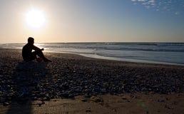 Peinzende mens op het strand Stock Fotografie