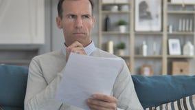 Peinzende Midden Oude Mens die terwijl het Lezen van Contract denken stock footage