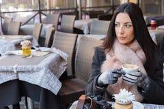 Peinzende, mooie en elegante vrouwenzitting op een Europese koffie Stock Foto's