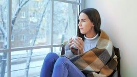 Peinzende mooie vrouwenzitting bij venster genieten die de winterscène bekijken stock footage