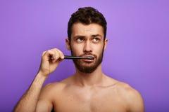 Peinzende nadenkende sexy kerel die opzij en zijn tanden borstelen eruit zien stock foto's