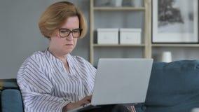 Peinzende oude hogere vrouw die en aan laptop denken werken stock videobeelden