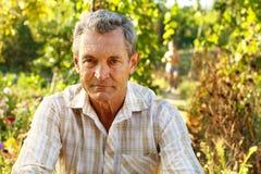 Peinzende oude mens in tuin Royalty-vrije Stock Foto's