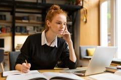 Peinzende rode haired tiener die laptop computer met behulp van royalty-vrije stock fotografie