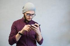 Peinzende teenaegerkerel die smartphone, over witte achtergrond gebruiken Gekleed in overhemd en zilveren hoed, die glazen dragen royalty-vrije stock afbeelding
