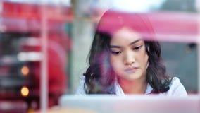 Peinzende toevallige Aziatische onderneemster die enthousiast het bekijken het scherm werken die laptop met behulp van stock video