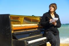 Peinzende vrouw bij de oude piano royalty-vrije stock foto's