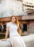 Peinzende vrouw die in de stad rust stock fotografie