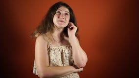 Peinzende vrouw die die en een idee denken hebben over oranje achtergrond wordt geïsoleerd stock footage