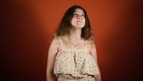 Peinzende vrouw die en een idee denkt heeft dat over oranje achtergrond wordt geïsoleerd stock videobeelden