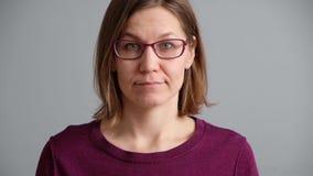 Peinzende vrouw die en een idee op grijze achtergrond denken hebben Mooie Kaukasische vrouw die sweater en glazen dragen stock footage