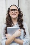 Peinzende in vrouw die met modieuze glazen haar tablet houden Stock Foto's