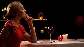 Peinzende vrouw die op vriend laat op romantisch diner in restaurant wachten stock foto's