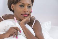Peinzende vrouw die resultaten van een zitting van de pregancytest op bed te weten komen stock afbeelding