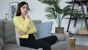 Peinzende vrouw die terwijl binnenshuis het zitten op bank denken stock video