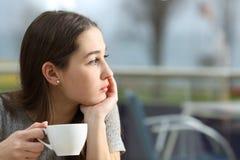 Peinzende vrouw die weg in een koffiewinkel kijken Stock Afbeeldingen