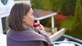 Peinzende vrouw die zich op balkon met kop die van koffie bevinden, op koude dag opwarmen stock afbeelding
