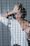 Peinzende vrouw in manchetten die zich achter rooster bevinden royalty-vrije stock fotografie