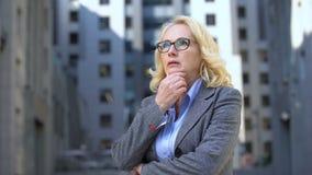 Peinzende vrouwelijke directeur in oogglazen die, het werkspanning, bezorgdheid zich in openlucht bevinden stock video